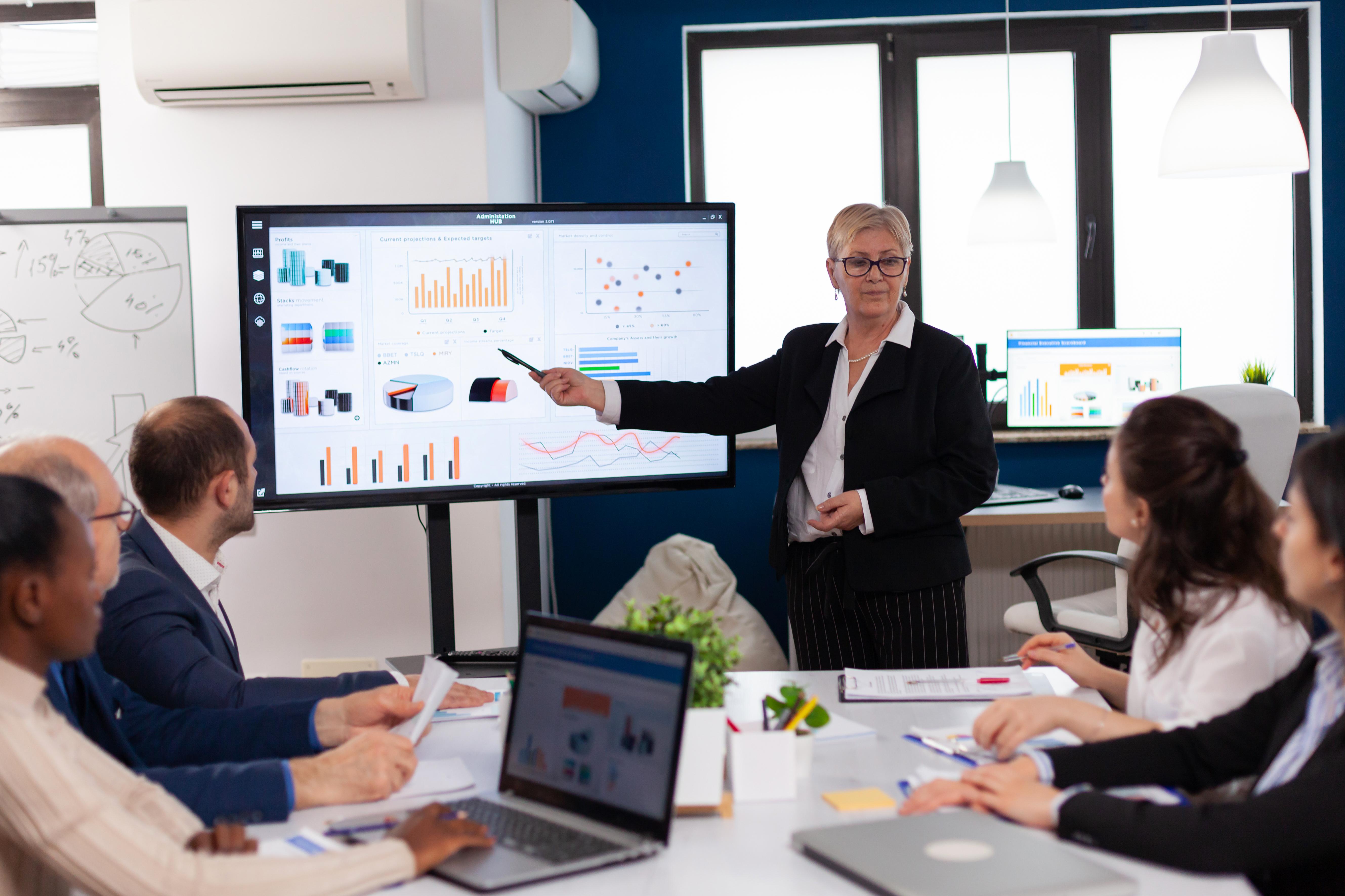 senior-startup-businesswoman-holding-presentatin-conference-room-briefing-graph-information.jpg