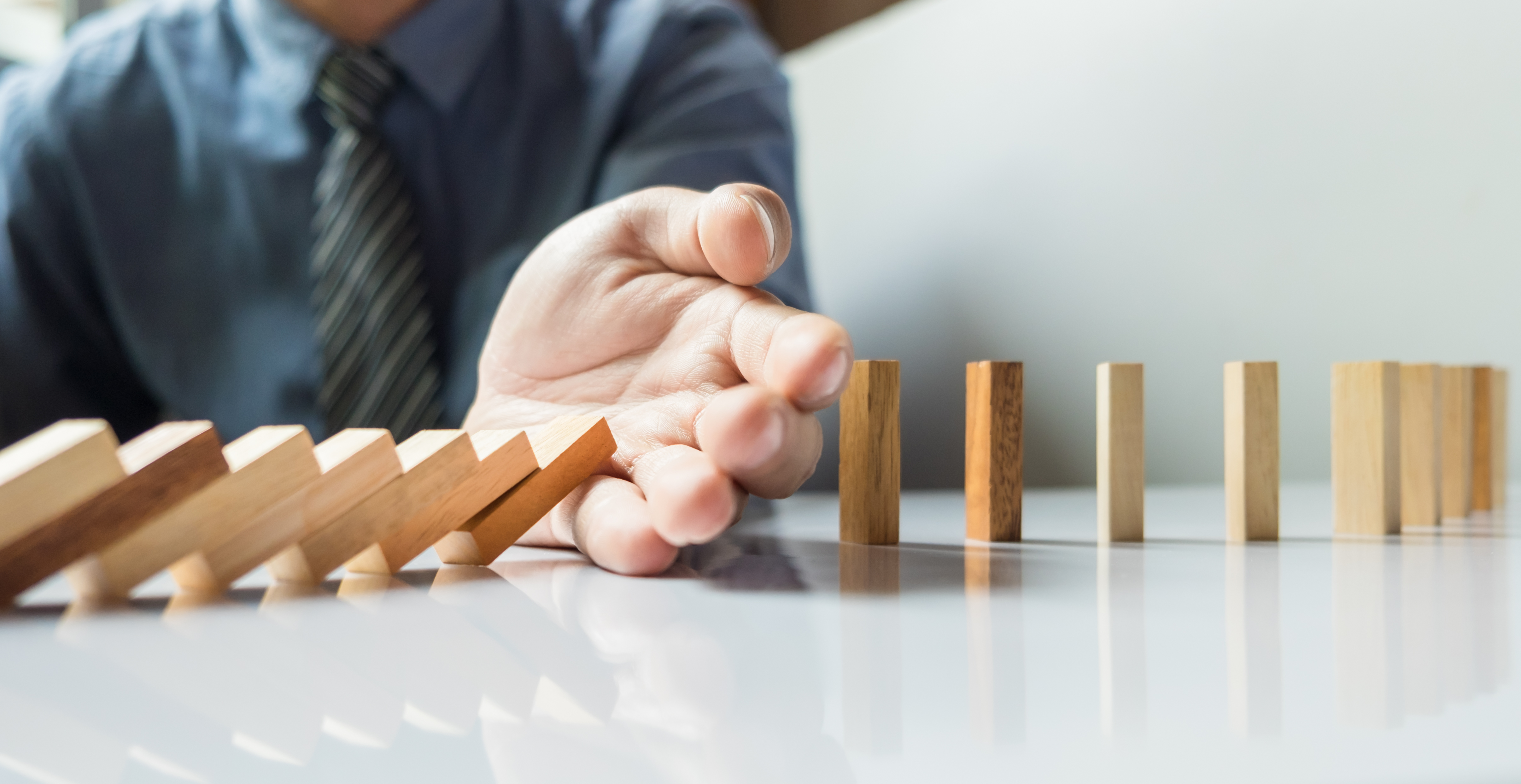 businessman-hand-stop-dominoes-continuous-toppled-risk-with-copyspace.jpg